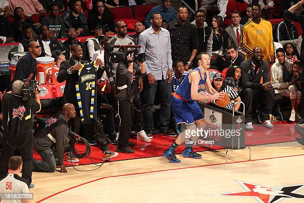 East Team Captain Dwyane Wade holds up Steve Novak's Marquette jersey while Novak of the New York Knicks competes in the 2013 Foot Locker ThreePoint...