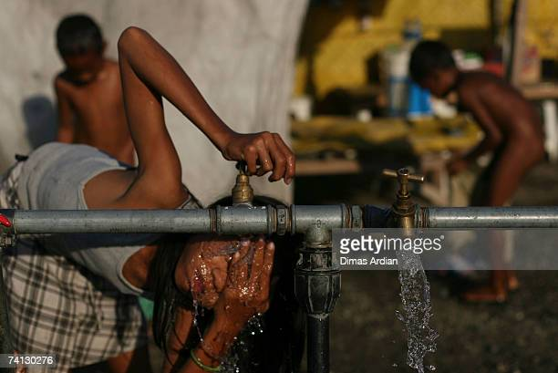 East Timorese children wash themselves in one of many refugee camps where hundreds of local people are displaced by the ongoing violence in East...