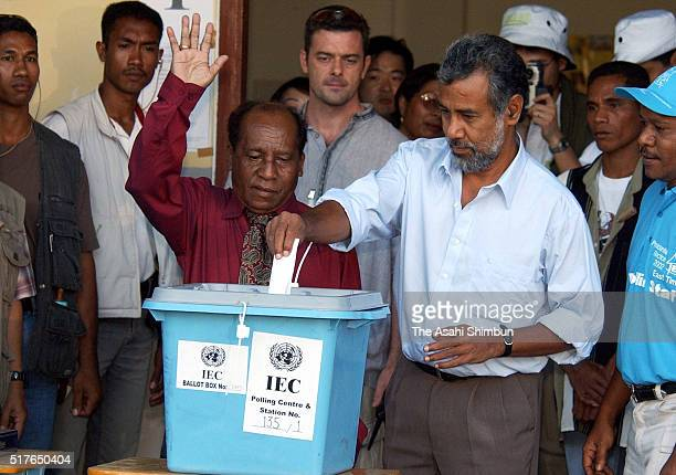 East Timorese independence leader Xanana Gusmao casts his vote into the ballot box while his rival Francisco Xavier Do Amaral waves at a polling...