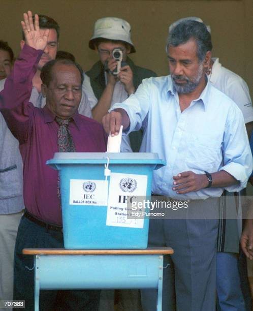 East Timorese independence leader Xanana Gusmao casts his vote into the ballot box while his rival Francisco Xavier Do Amaral waves April 14 2002 at...