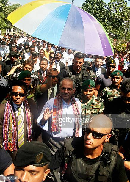 East Timorese President Jose RamosHorta is flanked by UN peacekeeping soldiers and local security personnel and wellwishers as he walks towards his...