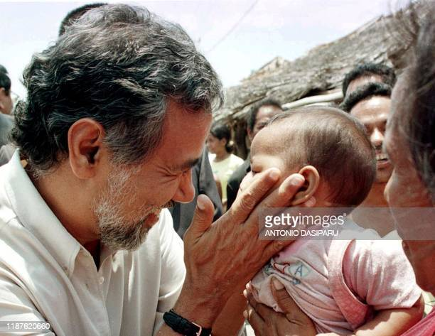 East Timorese President Xanana Gusmao touches a baby during a visit to a refugee camp in Nai Bontang Kupang West Timor 02 November 2002 President...