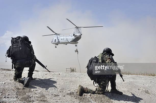 East Timorese soldiers of the Timor Leste Defense Force take up position on the shore as US Marines rappel from a US military helicopter during a one...