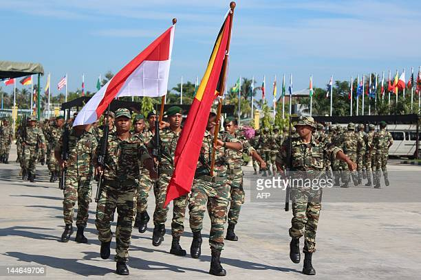 East Timorese troops parade carrying an Indonesian flag seen at left and the East Timor flag at right during rehearsals for the May 20 Independence...