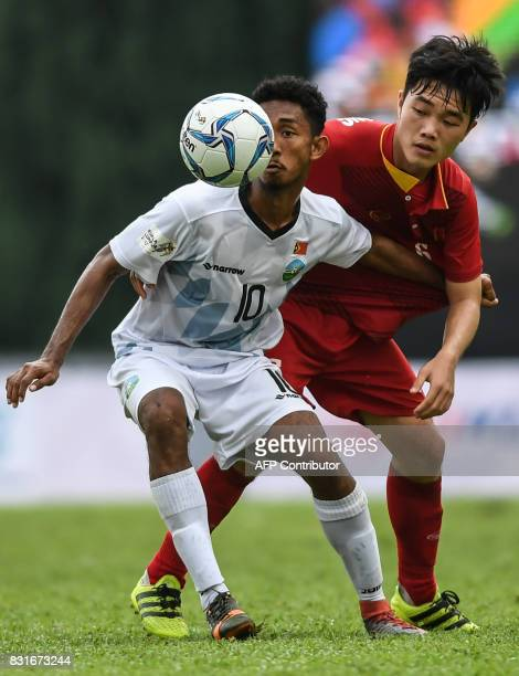 East Timor's Henrique Wilson Da Cruz Martins fights for the ball with Vietnam's Luong Xuan Truong during their men's football Group B round match at...