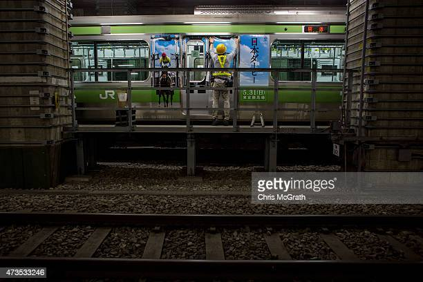 East Tokyo Media Services employee pastes an advertisement on the outside of a Yamanote Line train carriage at the JR East General Rolling Stock...