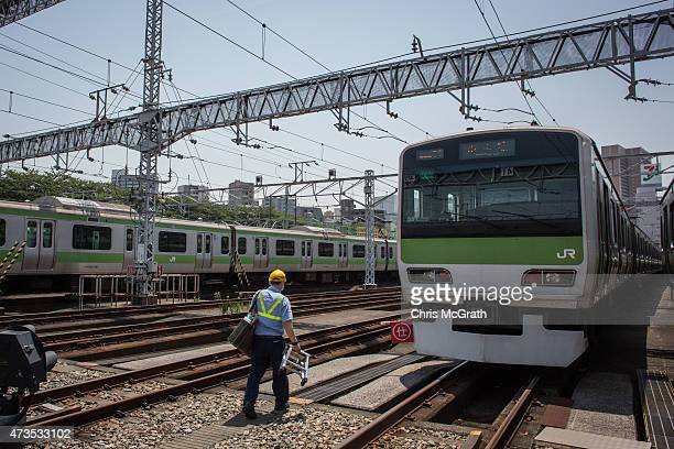 East Tokyo Media Services employee walks between trains as he replaces advertisements inside Yamanote Line train carriages at the JR East General...