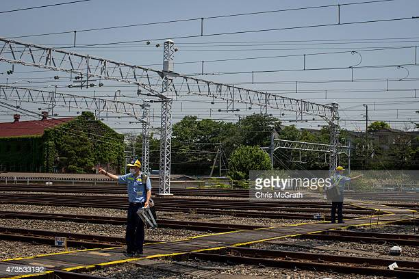 East Tokyo Media Services employees run through a safety check for incoming trains as they work between train tracks to replace advertisements inside...