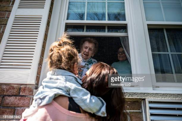 Sister Francis Piscatella of the Sisters of St. Dominic of Amityville says hello through a window to family members wishing her a happy 108th...