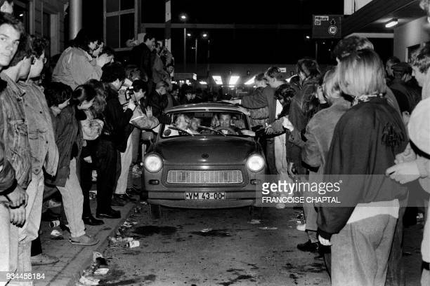 EastBerliner citizens are welcomed by the crowd as they enter WestBerlin by car at the Checkpoint Charlie on November 9 1989 After months of mass...