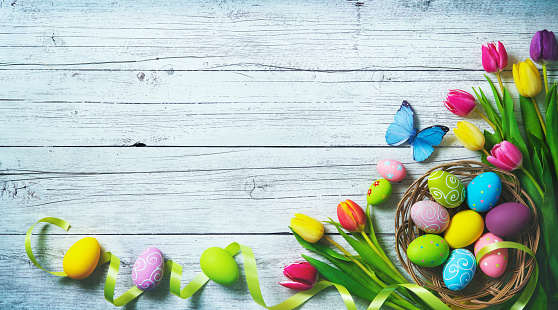 Easter background. Colorful spring tulips with butterflies and painted eggs 927031174