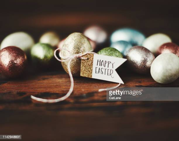 easter background with glittery easter eggs and happy easter message - easter stock pictures, royalty-free photos & images