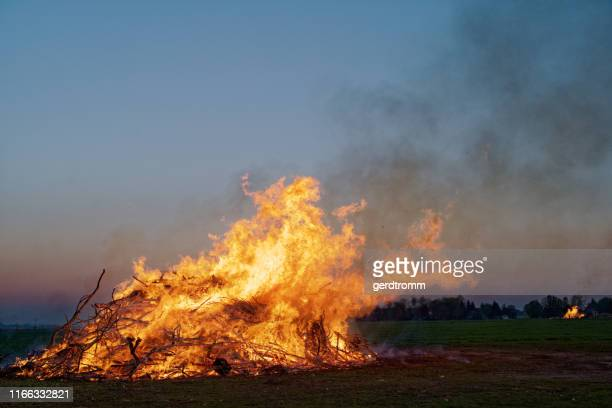 easter bonfires burning in a field, east frisia, lower saxony, germany - osterfeuer stock-fotos und bilder
