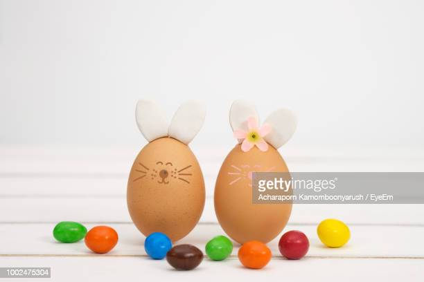 Easter Bunnies Made With Egg By Candies On Table Against White Background