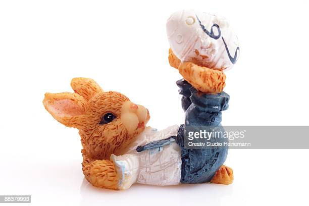 Easter bunny figurine balancing egg on feet, close-up