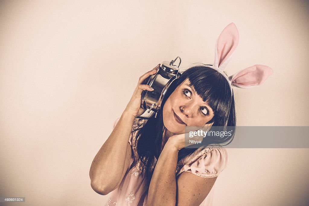 Easter Bunny weared Woman with Alarm Clock : Stock Photo