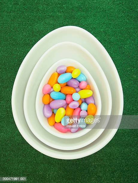 Easter candy in bowl atop stack of egg-shaped bowls, overhead view