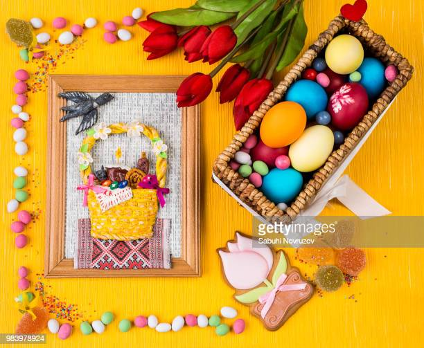 Easter colorful background. Painted eggs in a basket, sweets and flowers on a colored orange...