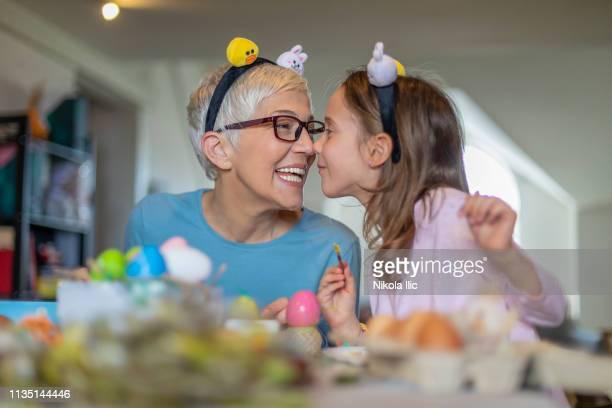 conceito de easter. a menina bonita feliz e a avó cinzenta do cabelo preparam ovos da galinha para o feriado - easter family - fotografias e filmes do acervo