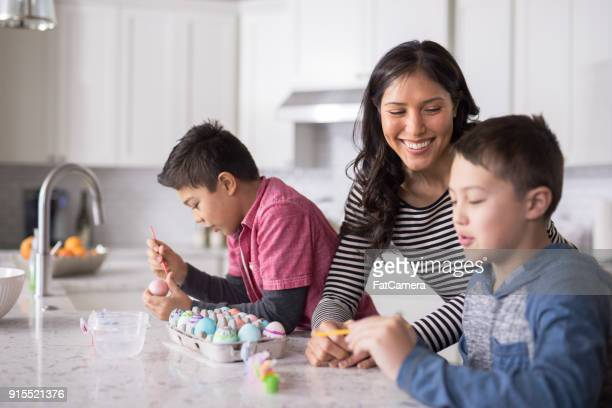 easter egg decorating in modern kitchen - happy easter mom stock pictures, royalty-free photos & images