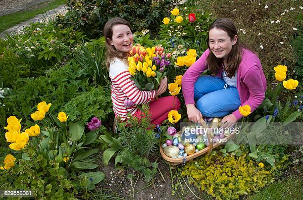 Easter egg hunt girls with their chocolate eggs and Spring flowers