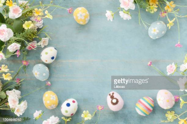 easter eggs and flowers on a rustic blue wood background - easter stock pictures, royalty-free photos & images