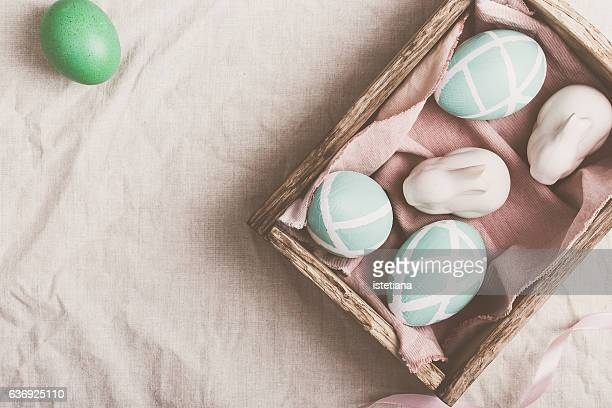 Easter  eggs and two porcelain bunnies on pastel background. Top view