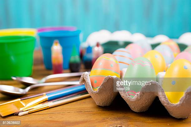 Easter eggs being decorated on wooden table. Supplies.