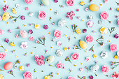 Easter eggs, colorful flowers on pastel blue background. Easter, spring concept. Flat lay, top view