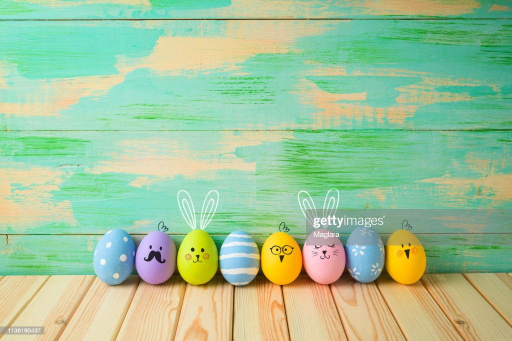 Easter eggs decorations on wooden table over colorful background : Stock Photo