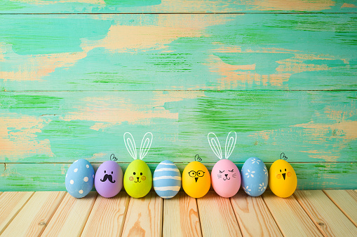 Easter eggs decorations on wooden table over colorful background 1136190437