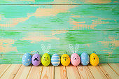 Easter eggs decorations on wooden table over colorful background