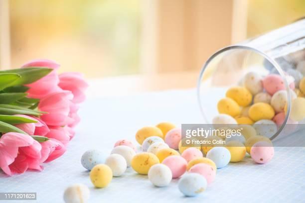easter eggs fallen from a glass jar and tulips bouquet - abril fotografías e imágenes de stock