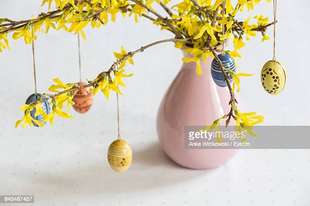 Easter Eggs Hanging On Flower Twigs In Vase On Table