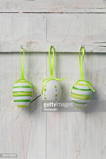 Easter eggs hanging on wooden door, close up