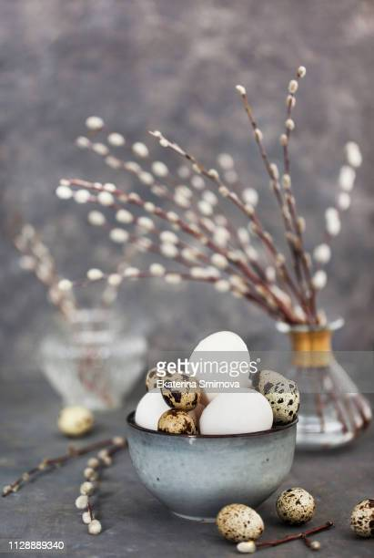 Easter eggs in bowl and willow bouquet on gray background