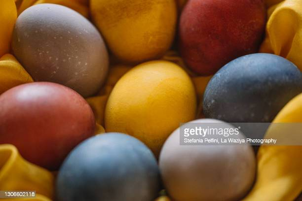 easter eggs naturally dyed on golden silk - dirty easter stock pictures, royalty-free photos & images