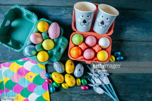 easter eggs on blue wooden table - easter egg stock pictures, royalty-free photos & images