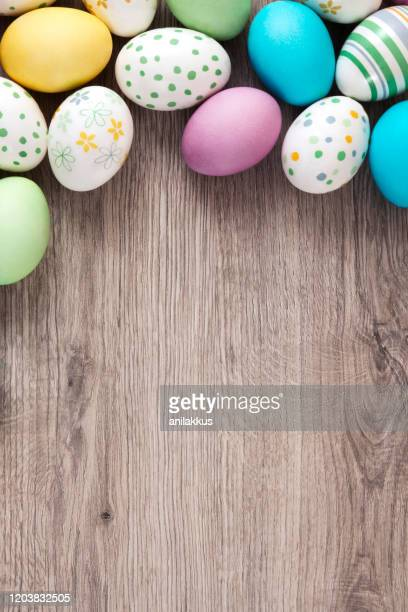 easter eggs on wooden background - easter stock pictures, royalty-free photos & images