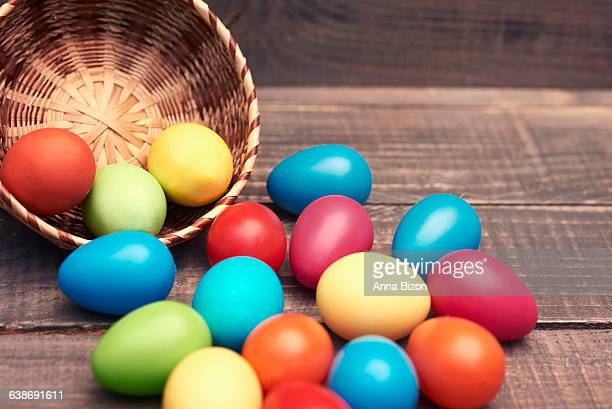 Easter eggs spilling out of their basket onto a wooden table. Debica, Poland