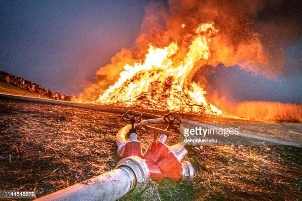 osterfeuer kontrollierte die verbrennung durch feuerwehr - osterfeuer stock-fotos und bilder
