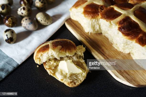 easter homemade hot cross buns, buttered with butter, quail unpainted eggs - hot cross bun stock pictures, royalty-free photos & images