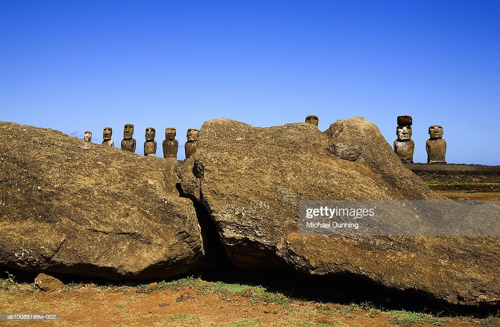 Easter Island, Ahu Tongafiki, row of ancient Moai statues behind rock : Stockfoto