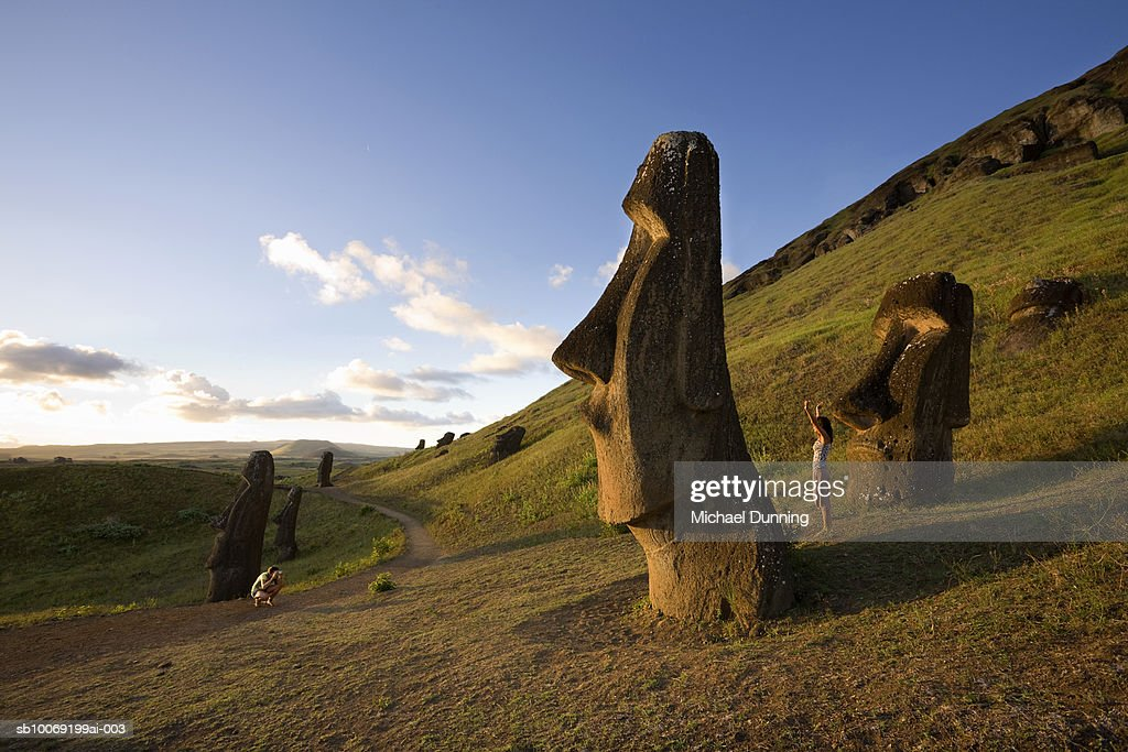 Easter Island, Rano Raraka, man photographing woman by ancient Moai statues : Stockfoto