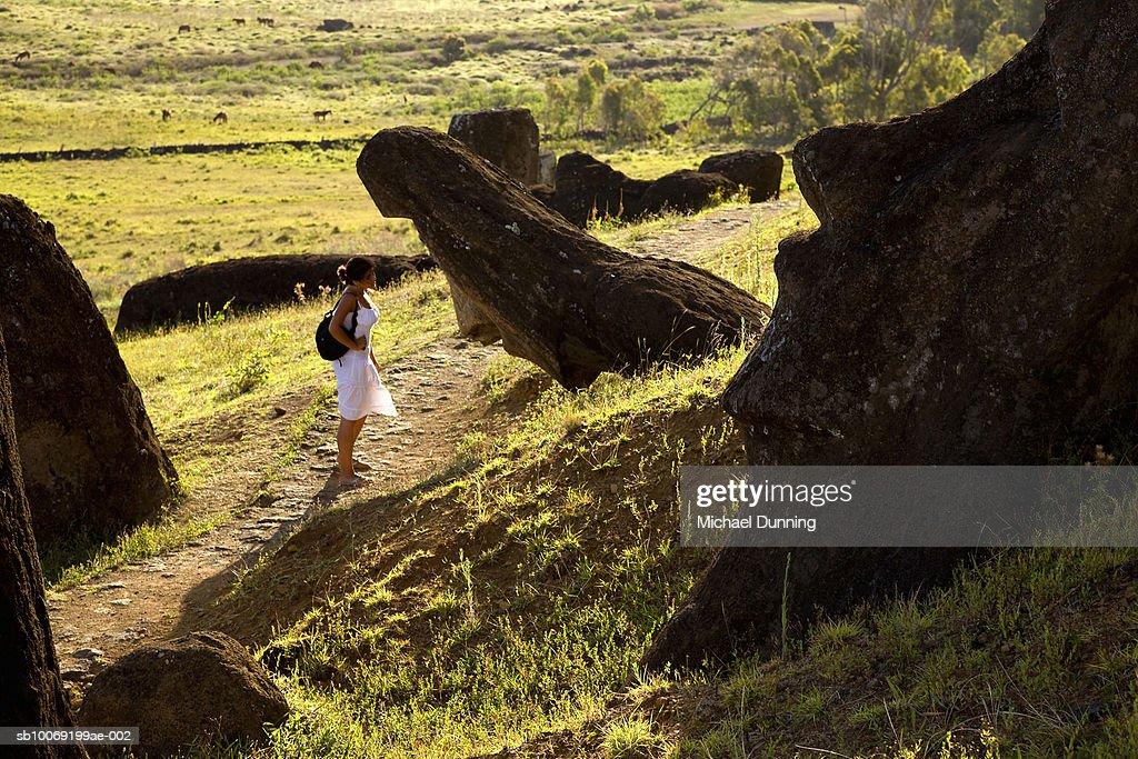 Easter Island, Rano Raraka, young woman observing ancient Moai statues : Stockfoto