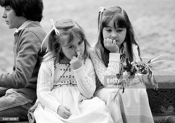 Easter, Passion Week, Palm Sunday 1981, church parade, little girl holds palm branches in the hand, another girl sits aside and picks her nose, aged...