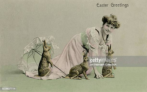 Easter postcard featuring photograph of young woman with three rabbits and parasol