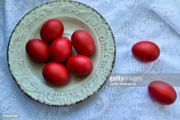 easter red eggs on plate - orthodox easter - easter orthodox stock photos and pictures