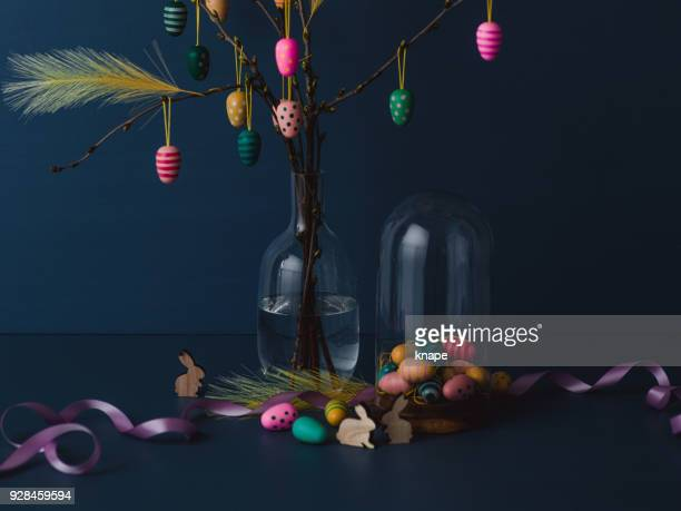 Easter still life with twigs and egg decorations with cruelty free artificial feathers on dark blue