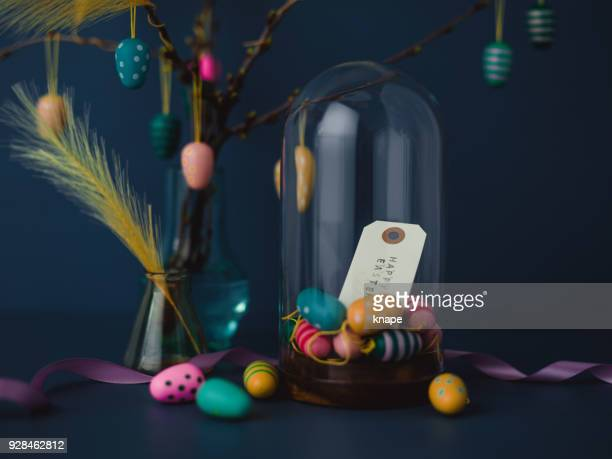 easter still life with twigs and egg decorations with cruelty free artificial feathers on dark blue - happy easter text stock pictures, royalty-free photos & images